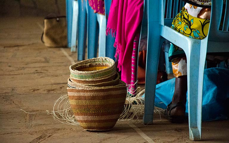 A trainee shares her knowledge with other basket weavers in a village